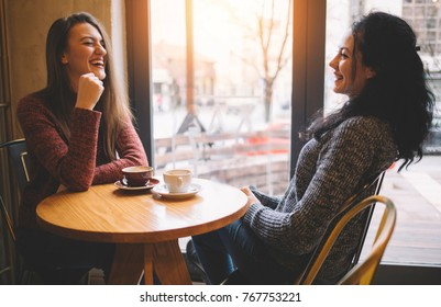 Two girls sitting in a bar, talking and laughing. They drink coffee.