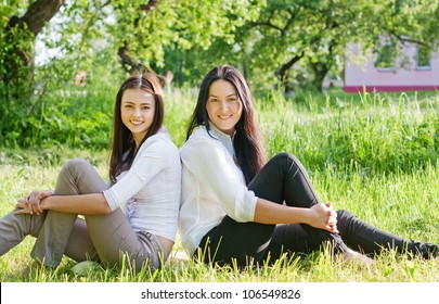 two girls sitting down on green grass