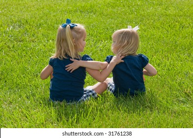 two girls sitting in the grass with arms around each other