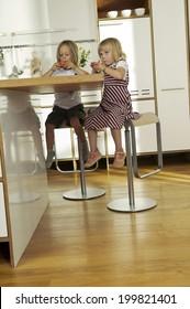 Two girls sitting in kitchen