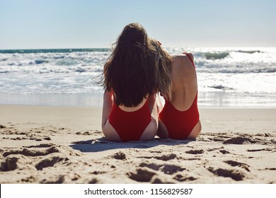 Two girls sitting on the beach in red swimsuits. Best friends concept.