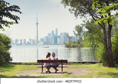 Two Girls sitting on the Bench, City View, Background, Toronto Islands, Toronto, Ontario, Canada