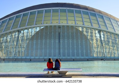 Two Girls Sitting on a Bench In Front of the Hemisferic - April 2017 - Valencia, Spain