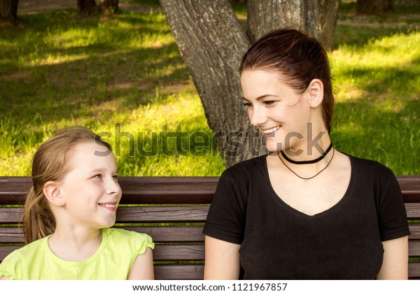 two girls are sitting on a bench talking and laughing