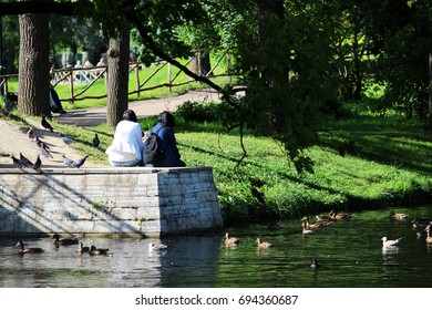 Two girls sitting on a concrete extension to the bridge and feeding ducks in a pond in a park.