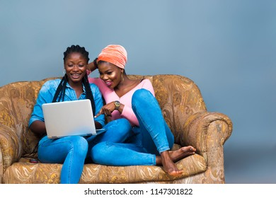 two girls sitting on a couch looking at a laptop