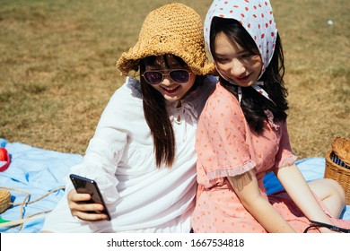 Two girls sitting on the field and watching the photo of this trip in smartphone.