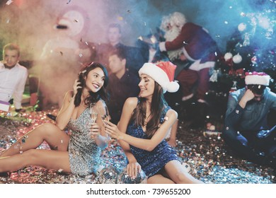 Two girls are sitting on the floor. Around them is scattered confetti. They rest after the party for the new year and laugh happily. They have glasses with champagne in their hands.