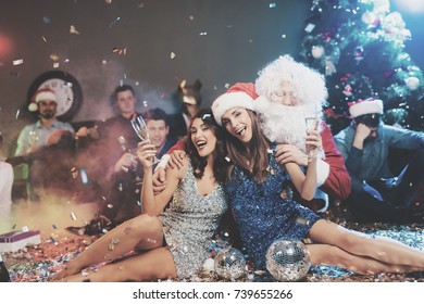 Two girls are sitting on the floor. Around them is scattered confetti. Next to them is a guy dressed as Santa Claus. Against the background sit and relax guys. They just had a rough New Year's party.