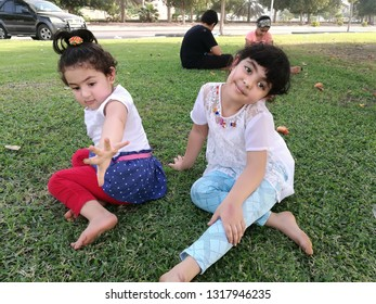 Two girls sitting on the green ground on the Palm Beach in Jubail Industrial City, Saudi Arabia in the summer of 2018