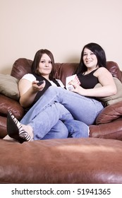 Two Girls Sitting on the Sofa Watching a Movie and Eating Pop Corn
