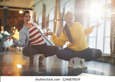 Two girls sitting on squats while doing hip hop or breakdance exercise in studio