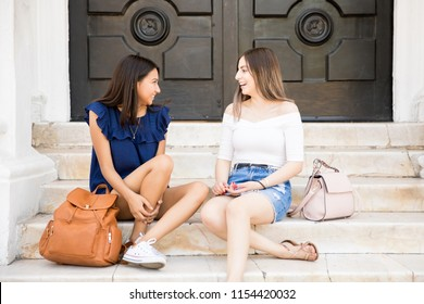 Two girls sitting outdoors gossiping and smiling