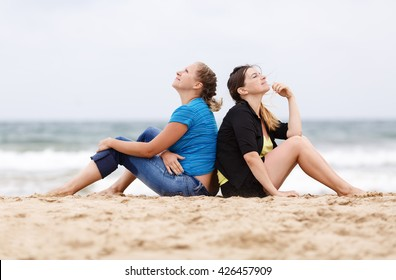 Two girls sitting outdoors. Two pretty young women sitting and relaxing on the sand on the beach. Selective focus on models.