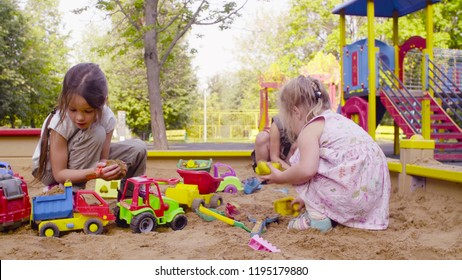 Two girls sitting in a sandbox and playing in the sand