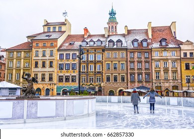 Two girls skate on a skating rink in the Old town square in Warsaw on the eve of Christmas, Poland.
