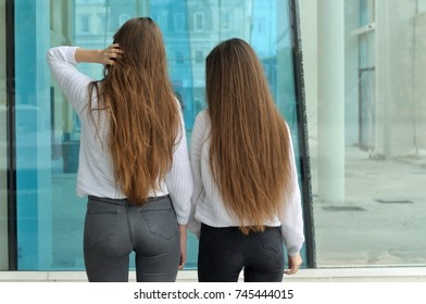 Two girls with a slender figure stand with their backs to the camera. They both have long brown hair that is long to the waist and they are dressed in identical white sweaters.
