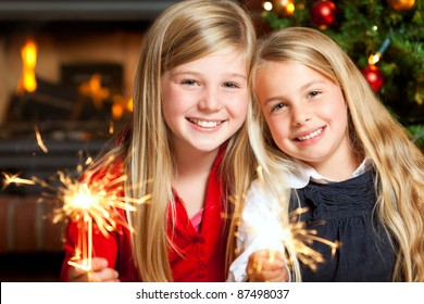 two girls with sparklers smiling