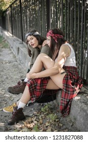 Two girls spend time together outdoors. The concept of difficult teenagers, bad students. Representatives of youth subcultures.