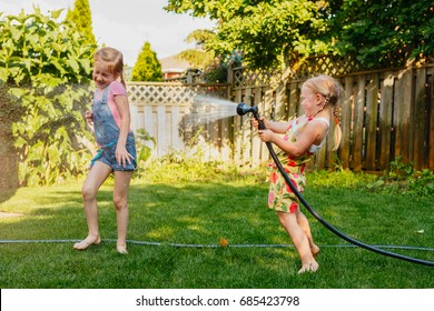Two girls splashing each other with gardening house on backyard on summer day. Children playing with water outside at sunset. Candid moment, lifestyle activity. Life friendship of sisters siblings.