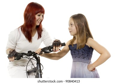 Two girls stand with a bicycle and talk