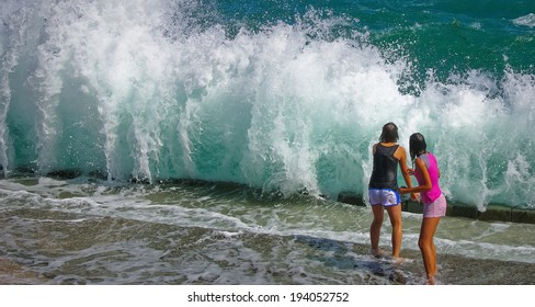 Two girls stand in front of sea wave in summer