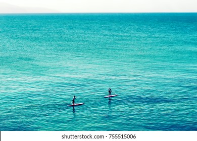 Two girls Stand up paddling in the open turquoise blue lagoon of Mediterranean Sea. SUP surfing in Greece, Crete island, Hersonissos.