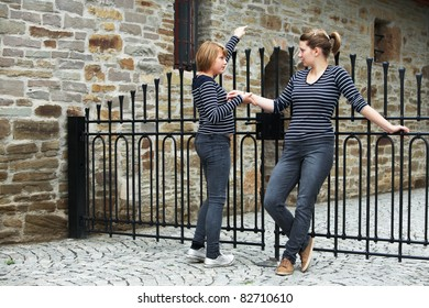 Two girls standing in front of closed gate