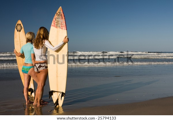 Two girls standing with surfboards at dawn looking out to the ocean