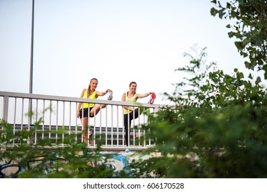 Two girls stretching on the bridge before an early morning workout.