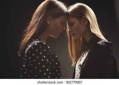 two girls studio portrait on dark background