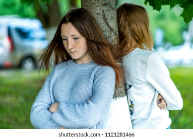 Two girls in summer in the park. The concept of school friends in a quarrel, a problem teenager. Emotions of conflict, discontent, resentment, frustration, anger. 2 sisters on the street in the city.