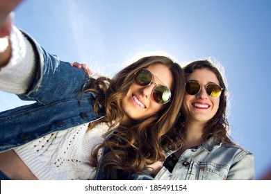 Two girls with sunglasses taking photos with a smartphone