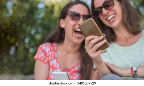 Two girls surprise social media unexpected youth millennial friendship media concept addiction to new technology trends lifestyle tech social generation having fun outdoors social trends park urban