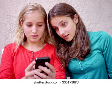 two girls surprised at a message on their phone