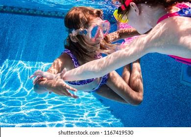 Two Girls Swimming in Pool