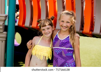 Two girls in swimsuit are having fun on the grass by the pool in summer
