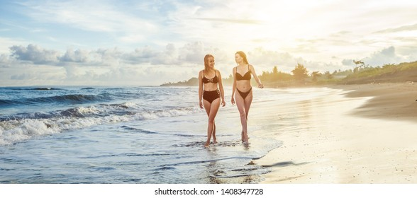 Two girls in a swimsuit on the beach. Banner panorama.
