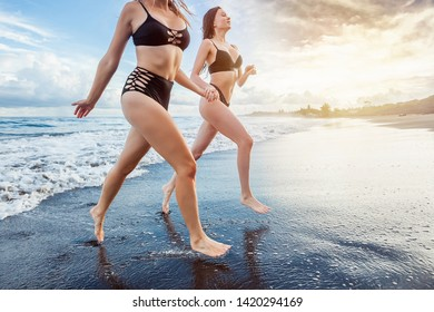 Two girls in swimsuits run along the beach.