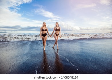 Two girls in swimsuits walk along the beach and hold hands.