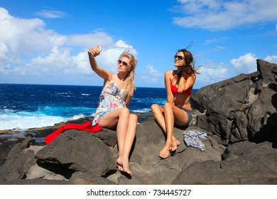 two girls taking photo on the beach in summer holidays and vacation