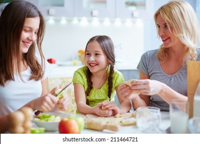 Two girls and their mother making patties