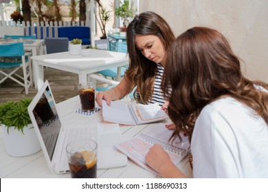 Two girls in their twenties studying on a terrace with a drink and a computer. They are two white girls with brown hair. Terrace in light colours and white wood furniture.