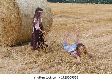 Zwei Mädchen werfen Heu auf einem Feld