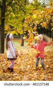 Two girls throwing leaves in autumn park