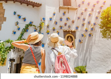 Two girls tourist admiring great view of flowerpots on the white walls on famous Flower street in Andalusia