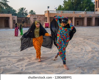 Two girls in traditional Qatari dress play together in a popular area of the ancient Qatari heritage, Doha, Qatar, May 09 2014