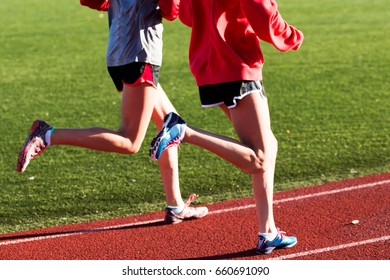 Two girls train for racing on a red track