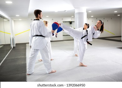 Two girls training taekwondo and kicking target pads improving their movement techniques