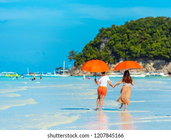 Two girls under umbrellas on a sandy beach, Boracay, Philippines. Copy space for text. Back view